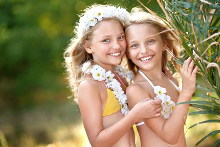 hula girl: portrait of two sisters twins in tropical style