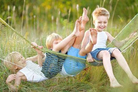 trois enfants qui jouent sur la prairie en été