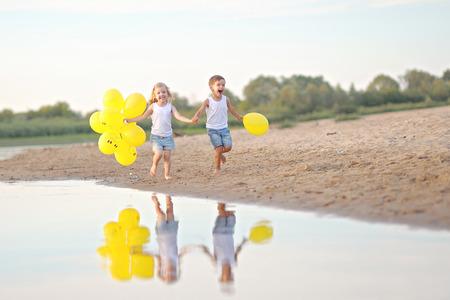 HAPPY FAMILY: Retrato de un ni�o y una ni�a en la playa en verano