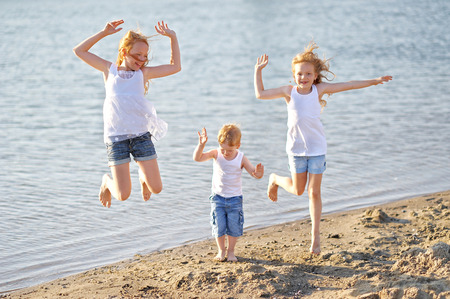 three children playing on beach in summer photo