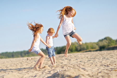 outside: three children playing on beach in summer