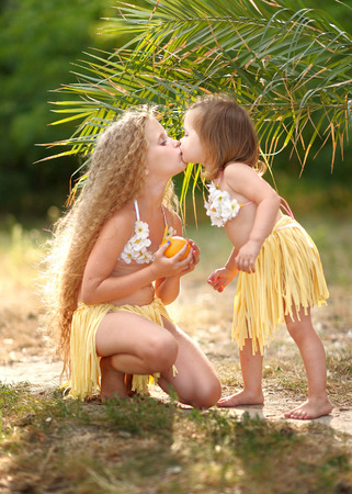 beach kiss: portrait of two sisters in tropical style Stock Photo