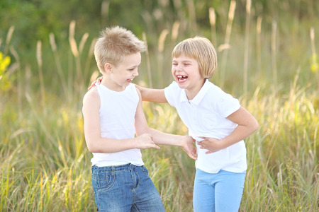 Portrait of a boy and girl on the meadow in summer photo