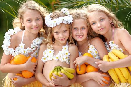 faldas: retrato de cuatro niñas en un estilo tropical Foto de archivo