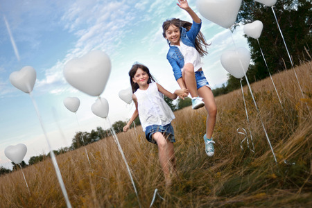 portrait of a little girls in a field with white balloons