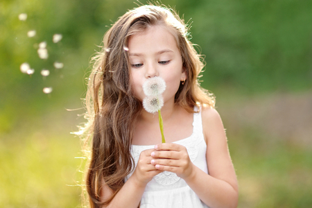 girl blowing: portrait of a beautiful little girl with flowers