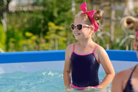 joyfulness: portrait of little girl in tropical style in a swimming pool Stock Photo