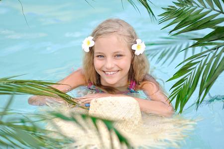 portrait of little girl in tropical style in a swimming pool Zdjęcie Seryjne