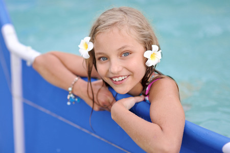 natural pool: portrait of little girl in tropical style in a swimming pool Stock Photo