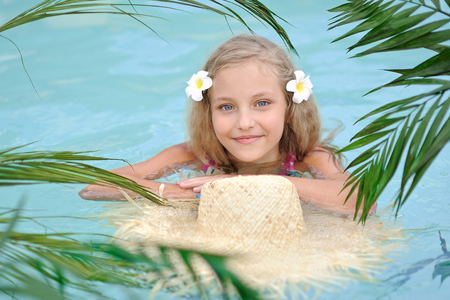 adorable child: portrait of little girl in tropical style in a swimming pool Stock Photo