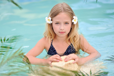 exhilaration: portrait of little girl in tropical style in a swimming pool Stock Photo