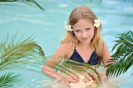 portrait of little girl in tropical style in a swimming pool Stock Photo