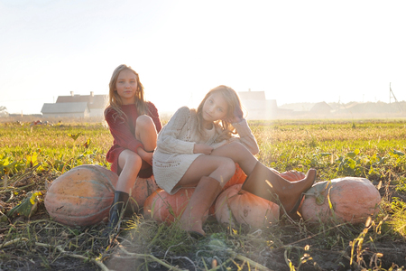 cinderella pumpkin: portrait of two sisters during the autumn harvest