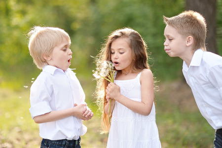 three children: three children playing on meadow in summer