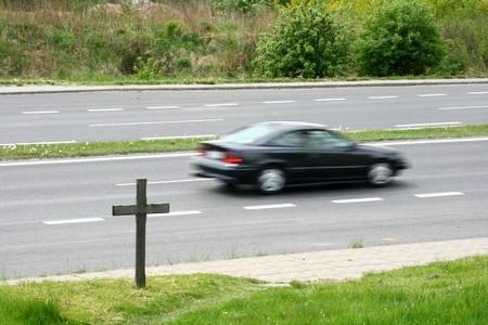 mortal danger: crucifix near the road Stock Photo