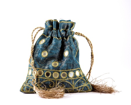 Decorative drawstring pouch in Indian textile, embroidered in gold silk and with mirrors and golden tassels. Isolated on a white background.