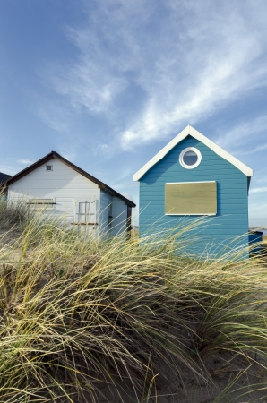 Beach huts and boats in sand dunes at Mudeford Spit on Hengistbury Head near Christchurch in Dorset  photo