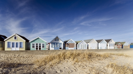 hengistbury: Brightly coloured row of beach huts on Mudeford Spit near Christchurch in Dorset