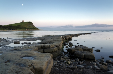 Kimmeridge Bay on Dorsets Jurassic coast, slate ledges revealed by a low tide and looking out towards Clavells Tower on the nearby headland. photo