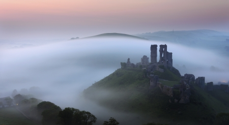 The ruins of Corfe Castle in Dorset rise out of the mist