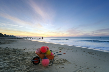 bournemouth: A wheelbarrow full of boat buoys on at Durley Chine beach with Bournemouth pier in the background  Stock Photo