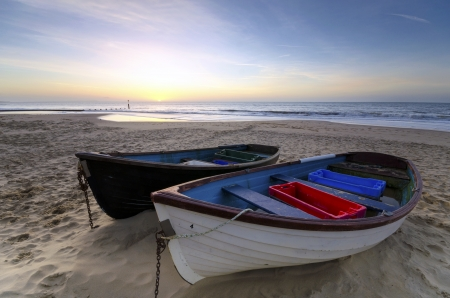 Vissersboten op het zand op strand van Bournemouth in Dorset bij zonsopgang Stockfoto