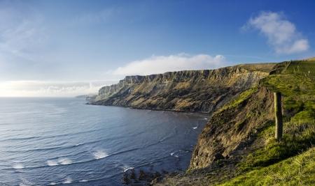 southwest: Gad Cliffs door Kimmeridge Bay aan de Jurassic Coast, het South West Coast Path is aan de rechterkant van het hek