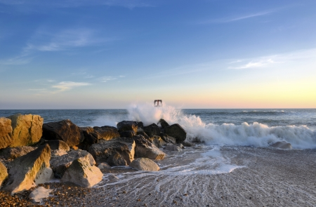 Waves hitting a sea groyne and rocks on the beach at Hengistbury Head near Bournemouth in Dorset Stock Photo