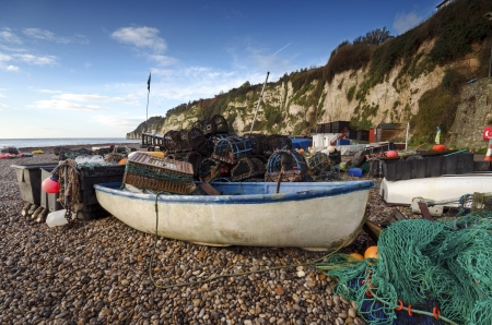 lobster pots: A fishing boat with nets and lobster pots on the beach at Beer on the Jurassic Coast in Devon