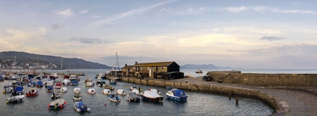lyme: Large panorama of the harbour at Lyme Regis in Dorset with The Cobb  harbour wall  boats and harbour buildings  Stock Photo