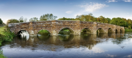 An historic ironstone bridge over the River Stour at Sturminster Marshall, near Wimborne Minster and reputedly the oldest bridge in Dorset. Stock Photo