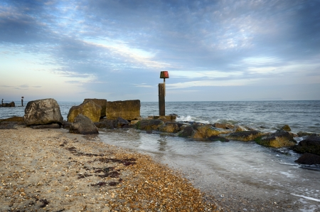 hengistbury: The beach, rocks and sea groynes at Hengistbury Head near Christchurch in Dorset