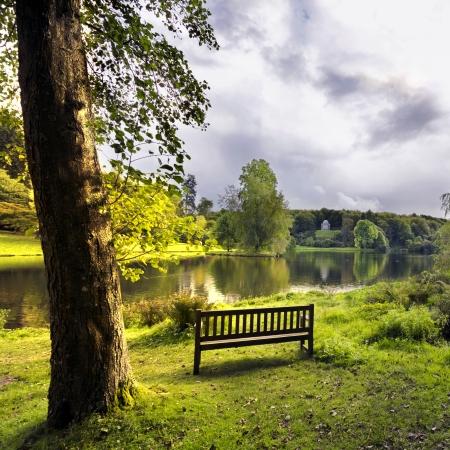Een bankje met uitzicht op het meer van Stourhead Stockfoto