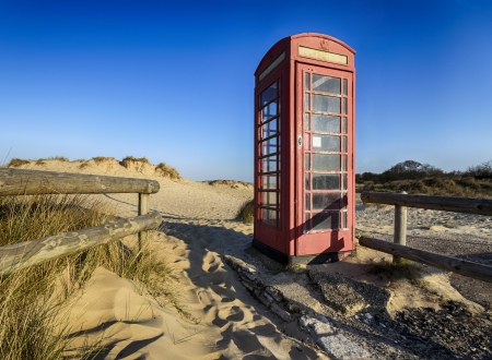Old red phone box on the beach at Studland in Dorset photo