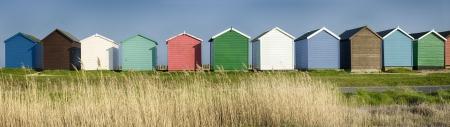 Een rij van kleurrijke strandhuisjes op de kust bij Calshot in Hampshire Stockfoto