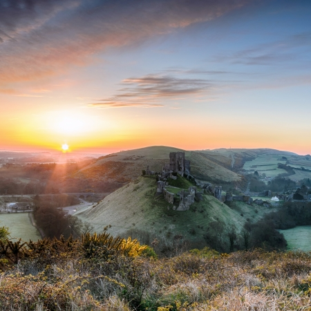 Sunrise overlooking the ruins of Corfe Castle on the Isle of Purpeck in Dorset. photo