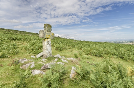 An ancient granite stone cross on a hillside on Bodmin Moor in Cornwall photo