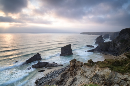 landslip: The treacherous cliffs and beach at high tide at Bedruthan Steps also known as Carnewas in Cornwall