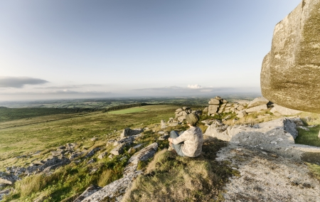 bodmin: Woman sitting on top of Kilmar Tor on Bodmin Moor in Cornwall, vintage effect