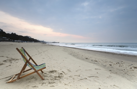bournemouth: A solitary deck chair at day break on Bournemouth Beach Stock Photo