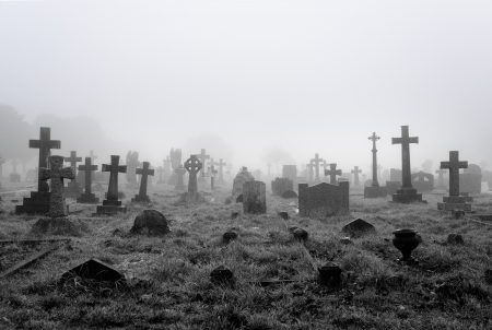 Spooky foggy ancient cemetery halloween background Stock Photo