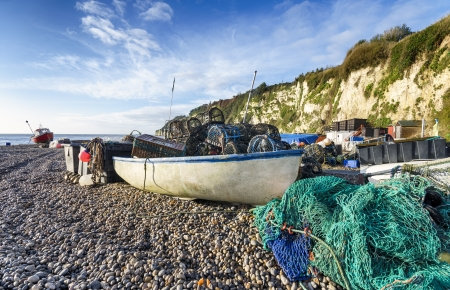 lobster pots: Fishing boats,  lobster pots and nets on the beach at Beer on Devon Stock Photo