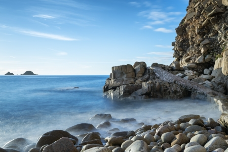 end of a long day: The beach and cliffs of Porth Nanven Cove near St Just in Cornwall also known as the Dinosaur egg beach after its large rounded cobbles  Stock Photo