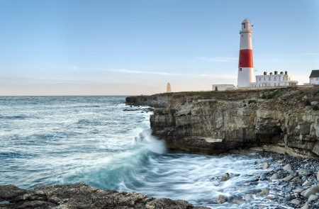 Waves crashing over rocks at Portland Bill lighthouse on the Jurassic Coast in Dorset Stock Photo