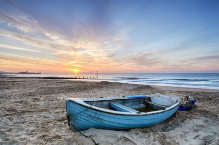 Turquoise blue fishing boat at sunrise on Bournemouth beach with pier in far distance