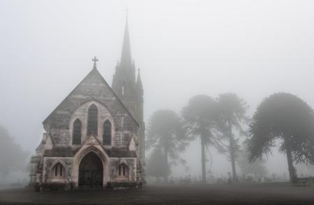소름 끼치는 안개가 자욱한 묘지에있는 오래된 교회 스톡 콘텐츠