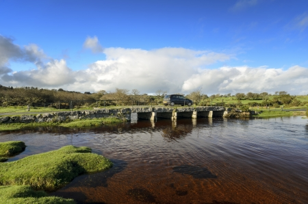 Motion blurred car driving on Delphi clapper bridge over the De Lank River near St Breward on Bodmin moor photo