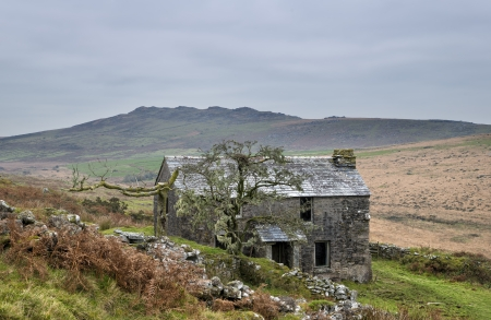 Abandoned farm house on Garrow Tor a remote part of Bodmin Moor in Cornwall, with Brown Willy in the background photo