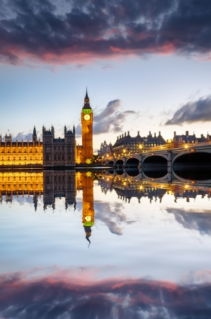 The Houses of Parliament, Big Ben and Westminster Bridge under a fiery sunset sky photo