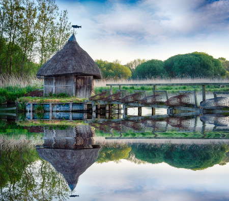 Thatched fisherman s hut and traditional eel traps on the River Test in Hampshire photo